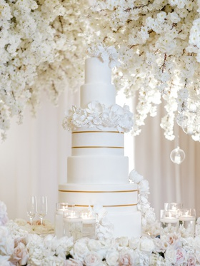 five tier wedding cake with two tiers of gold stripes and a layer of sugar flowers