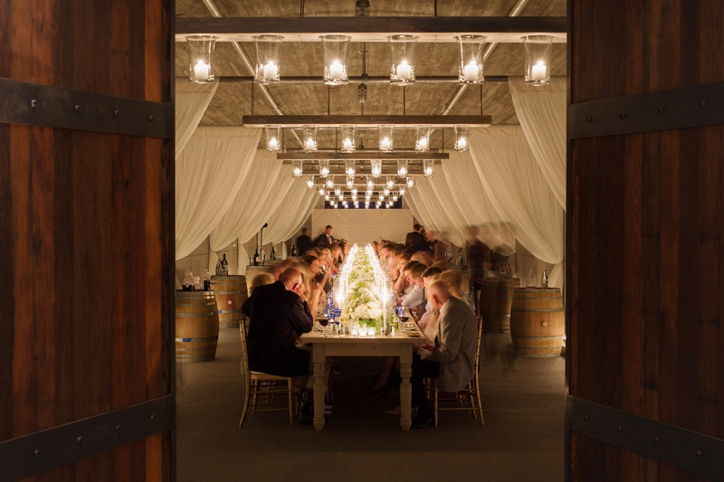 Guests in vineyard wine barrel room at long table