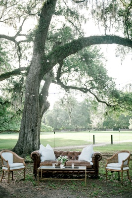 wedding reception lounge area under tree leather chesterfield sofa white wood cane armchairs bistro