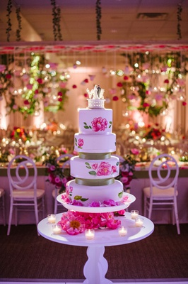 four layer white cake with pink flower design hand painted green ribbon in between