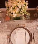 white table linens and china plateware with low white floral arrangements on mirror stand