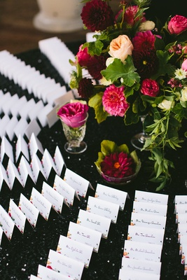 escort cards around flowers on black sequin table cloth linen