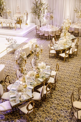 wedding reception ballroom tahir whitehead mirror serpentine table gold chairs tall centerpieces