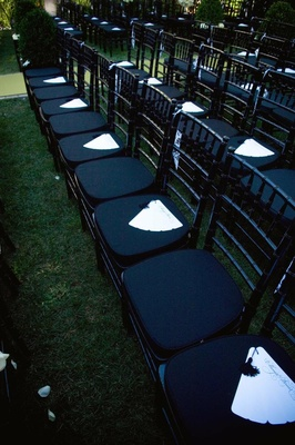 White fan-style wedding program on ceremony chairs