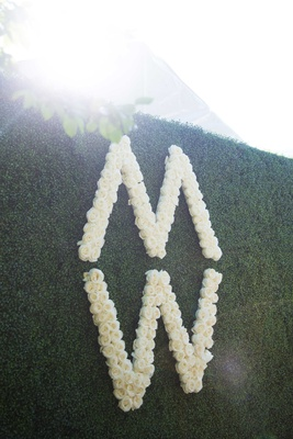 M and W initials in roses on green hedge wall for wedding reception