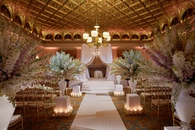 Gold wedding ballroom paneling with white delphinium flowers along aisle