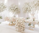 lush florals covering gold sweetheart table, full trees of florals