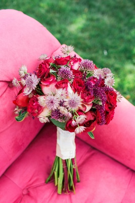 red pink purple flowers bouquet floral arrangement on pink couch outside roses peonies dahlias