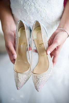 bride holding christian louboutin bridal heels pointed toe clear with rhinestone details