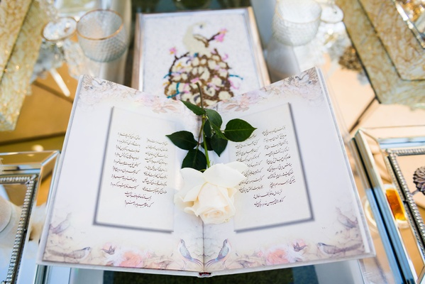 White rose on book with flower print border and farsi language script on sofreh table persian