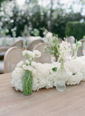 Wood table with hydrangea table runner and white flowers