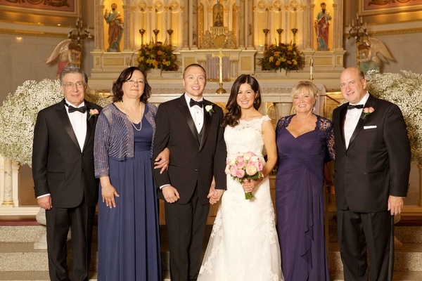 Bride and groom at front of church with family fathers in tuxedos and mothers in purple hued gowns