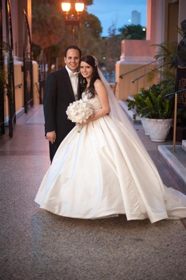 Bride in ball gown and groom smile in Florida