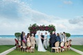 wedding ceremony beach grass lawn overlooking ocean greenery arch pink rose flowers wood chair small