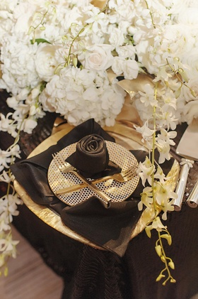 black napkin rose, polka dotted plate, gold flatware
