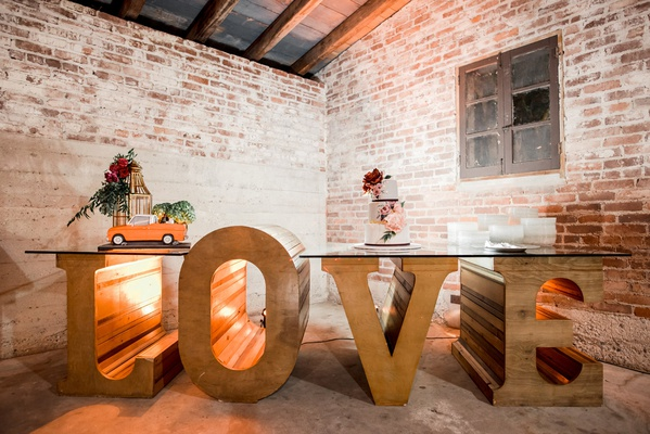large wooden letters spelling love with glass top to make dessert table