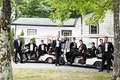 groom and groomsmen before wedding ceremony on large golf carts at summer camp theme wedding weekend