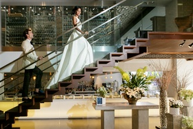 bride in inbal dror ball gown, groom in white tuxedo jacket, walking up stairs
