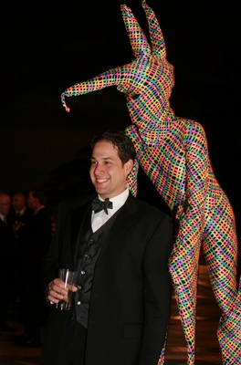 Man on stilts in bright costume surprises wedding guests