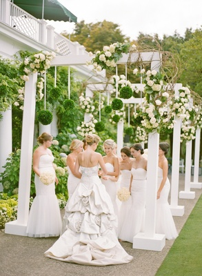 White bridesmaid dresses at flower arch reception
