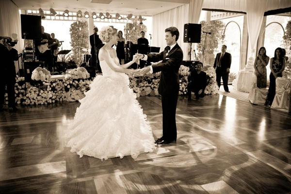 Black and white photo of newlyweds dancing and stage
