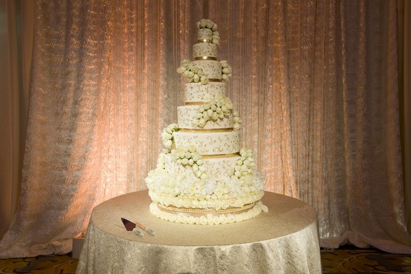 White wedding cake with gold bands and swirls and white roses