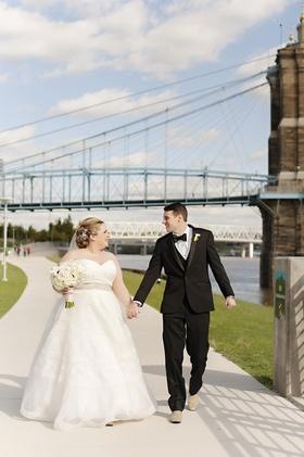 bride in strapless sweetheart watters wedding dress, groom in michael kors tux, bridge