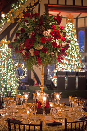 Gold wedding reception table with tall red, green, and white flower arrangement and Christmas trees