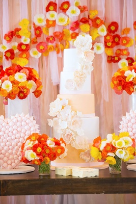Tall cake with sugar flowers on dessert table decorated with poppy flowers and drapes behind