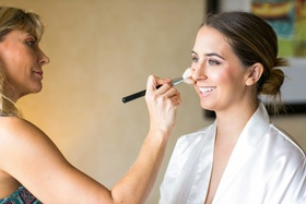bride in white robe has makeup applied on her wedding day
