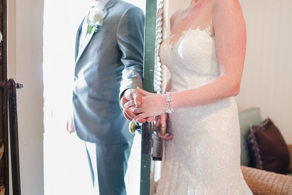 bride and groom hold hands around a door before ceremony bride in diamond bracelet