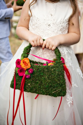 wedding ceremony flower girl in ball gown with mosss handbag purse and basket with pink ribbon