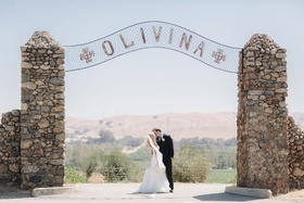 Bride in Hayley Paige dress kisses groom at Olivina stone gate