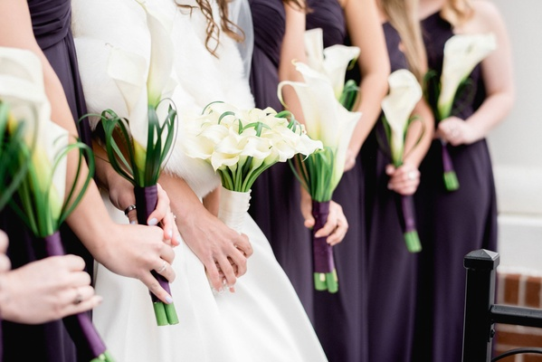 Bride and bridesmaids carrying white calla lily bouquet nosegay flowers wrapped with white purple