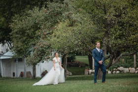 wedding photo first look bride in lace dress overskirt groom in navy suit pink tie waiting by tree