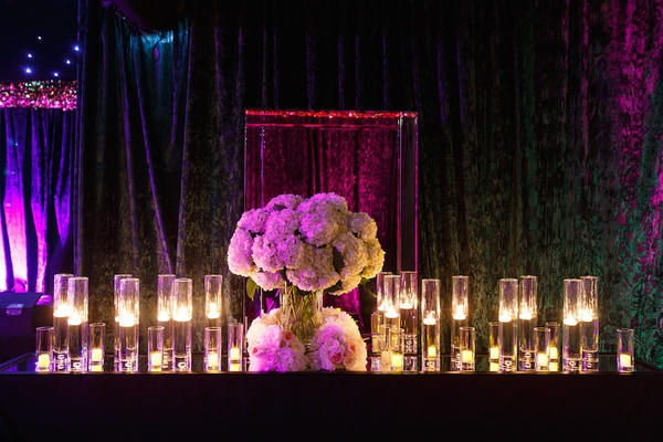 Wedding reception tent with mirror-top table, floating, votive candles, white hydrangeas, roses
