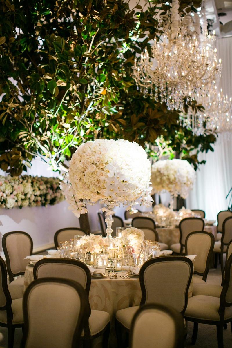 Magnolia trees in ballroom with white wedding centerpiece