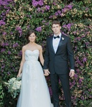 bride and groom hold hands in front of purple flowers