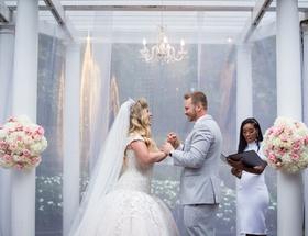 wedding ceremony female officiant drop waist ball gown tiara veil white pink flower chandelier