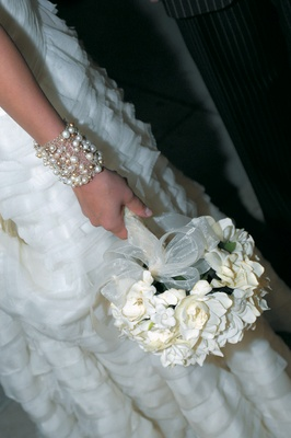 bride wearing bracelet holds white flower bouquet