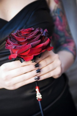 Bridesmaid holds a single black Baccara rose
