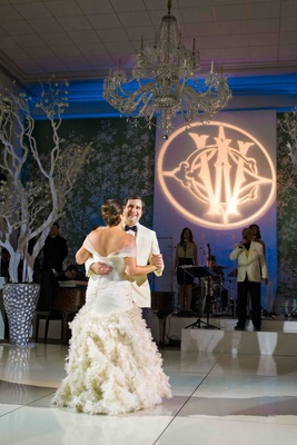 Bride and groom first dance on white floor in wallpaper room