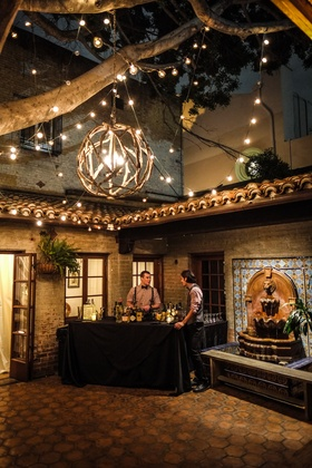 carondelet house courtyard with wooden chandelier and lights, bar