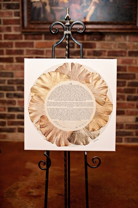Jewish wedding ketubah with golden petals to form a flower shape on iron stand
