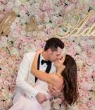 bride in blush wedding dress, groom in white tuxedo kiss in front of flower wall