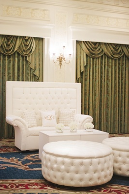 Ballroom wedding lounge with tufted white settee and ottoman