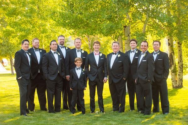 Groom in pink bow tie with groomsmen and ring bearer in blue grey bow ties