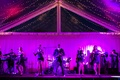Singers on stage illuminated by purple lighting