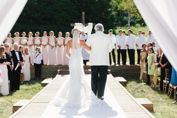 Wedding ceremony father of bride walking her down aisle white aisle runner outdoor ceremony cross