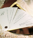 White fan-style menu on top of gold dinner plate
